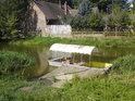 Plovoucí molo s malou bárkou na levém břehu Staré Moravy v Hodoníně.