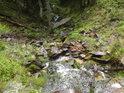 Ocelová trubka ještě kouká z propustu, ale horská bystřina se prudce valí mezi kameny.