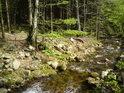 Levý břeh Moravy tvoří kameny a stromy.